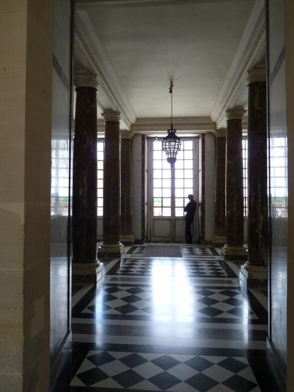 silhouette méditative devant une fenêtre, dallage noir et blanc en damier